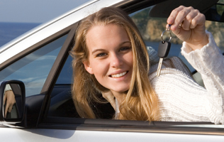 woman in a car holding up the key