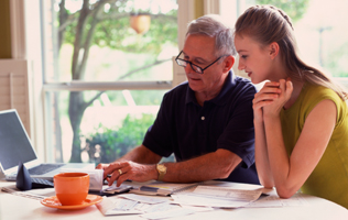 older man showing adult daughter how to balance a checkbook